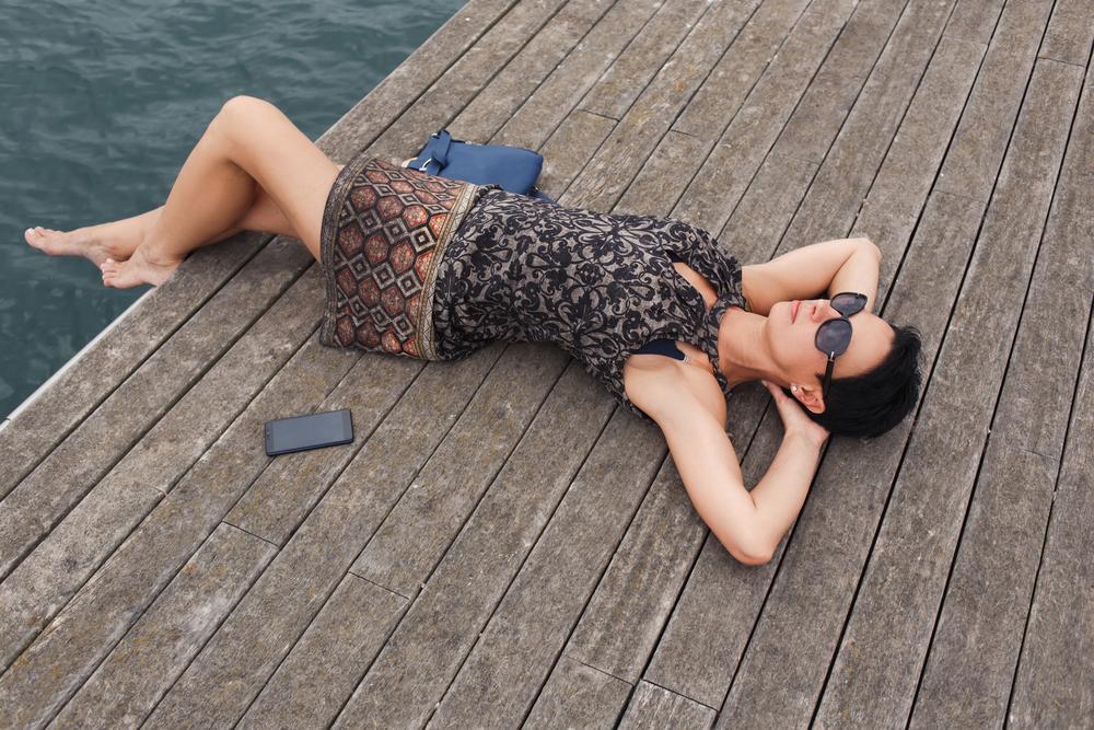 Женщина мечтает лежа на пирсе