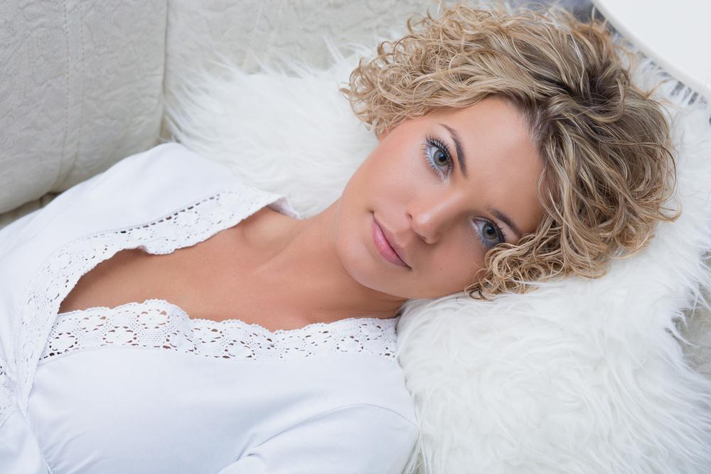 Красивая девушка лежит на диване