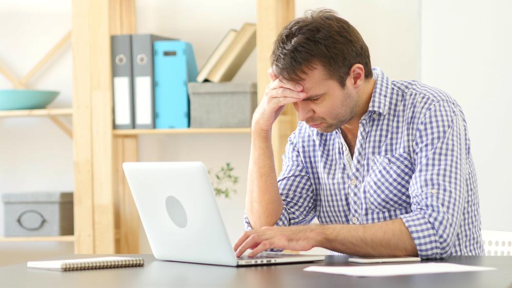мужчина грустит за ноутбуком