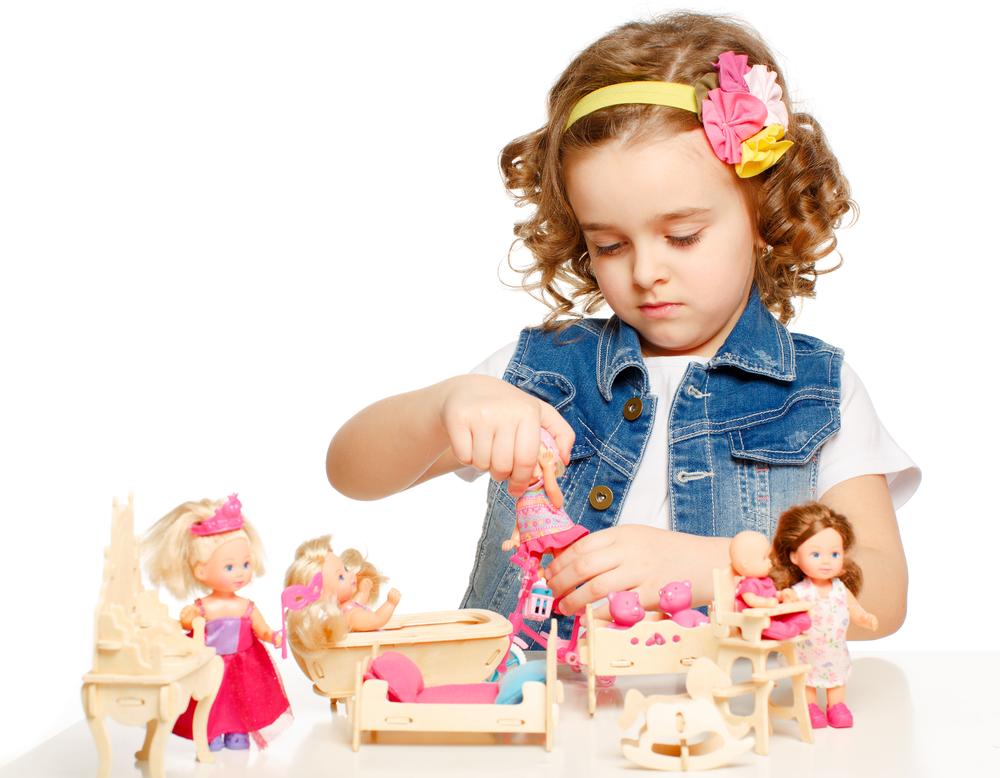 маленькая девочка играет с куклами