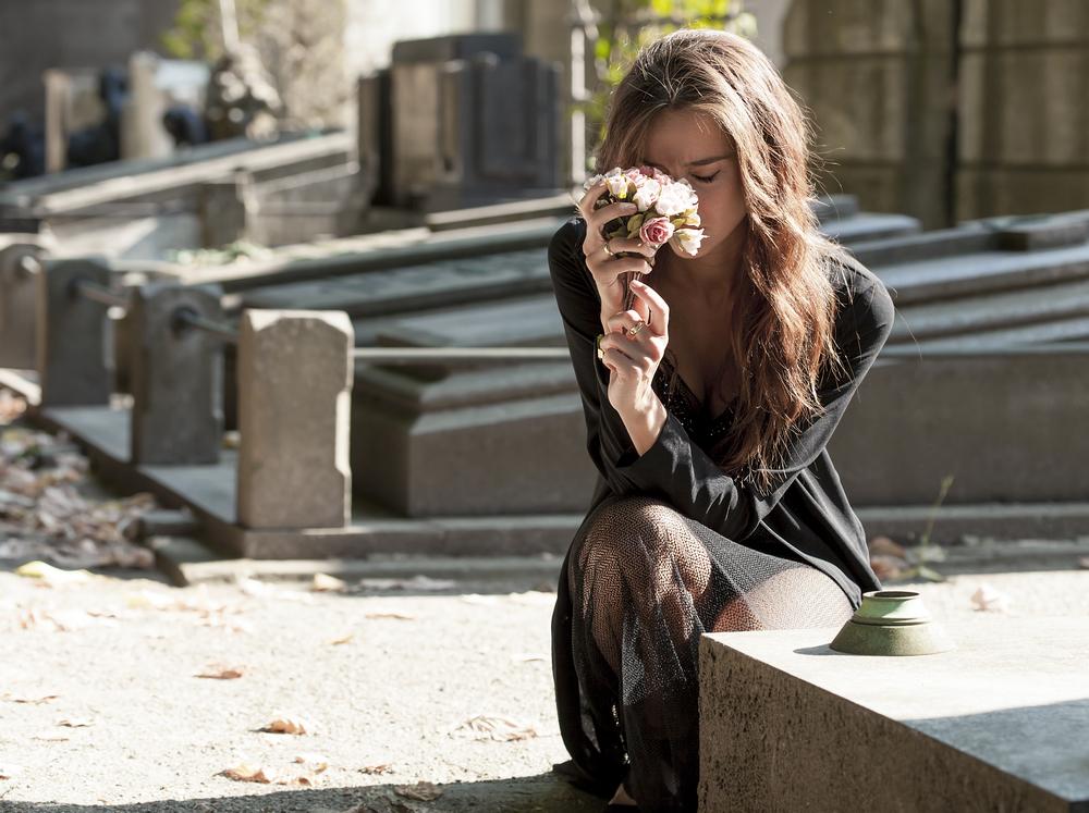 женщина скорбит на могиле отца
