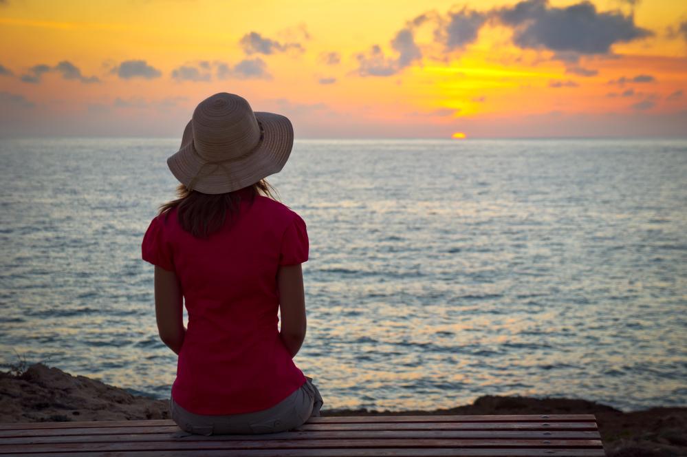 молодая женщина испытывает ностальгию глядя на закат