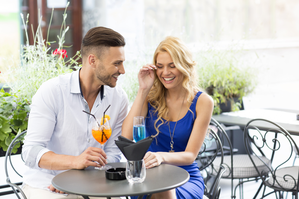 молодая пара смеется за столом сквозь слезы