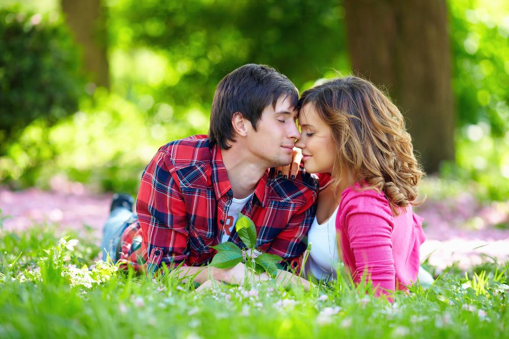 красивая влюбленная пара лежит на траве