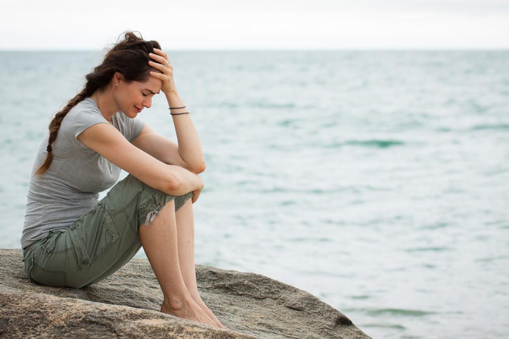 одинокая девушка плачет на берегу моря