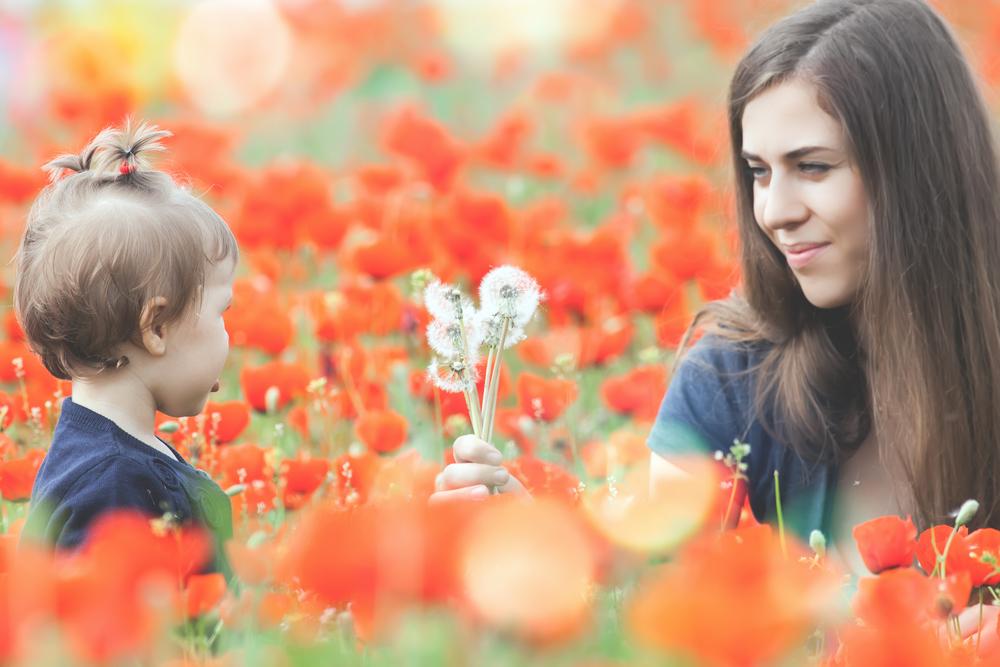 мама играет с ребенком в поле