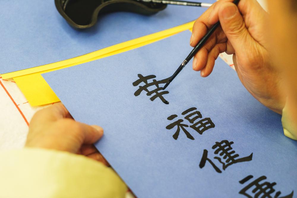 Пишут на бумаге японские иероглифы