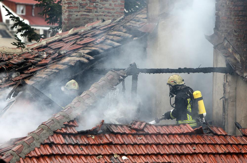 Пожарные тушат горящий дом