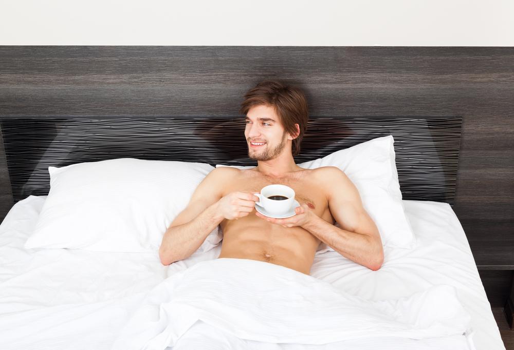 Мужчина утром в постели с кофе