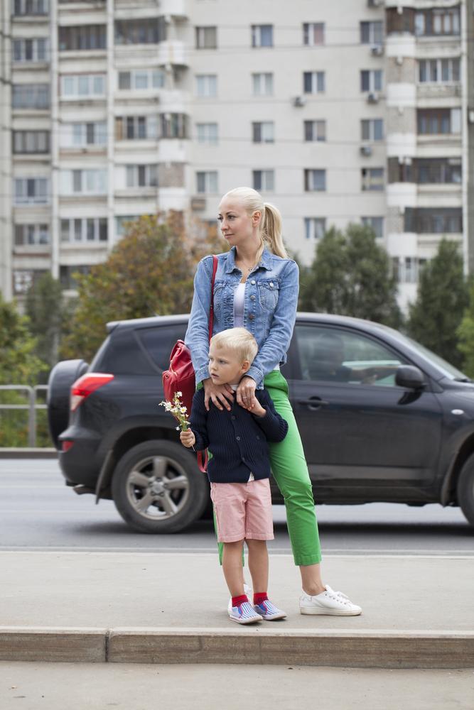 мать и сын ждут общественный транспорт на дороге