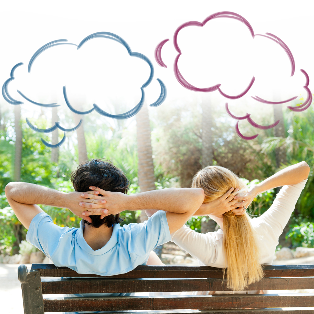 молодая пара сидит на скамейке и мечтает