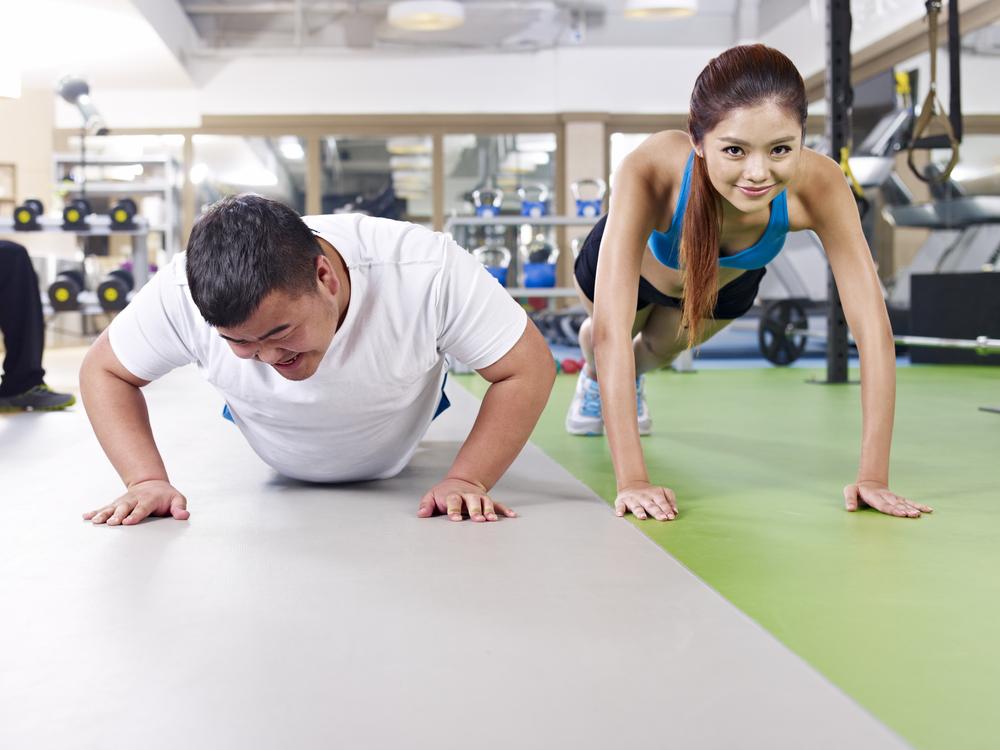 мужчина сдался а женщина продолжает заниматься тренировкой