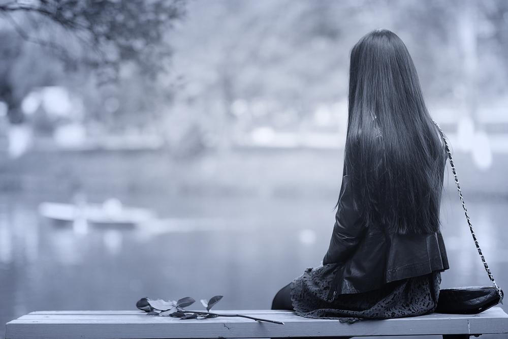 одинокая девушка сидит на скамейке