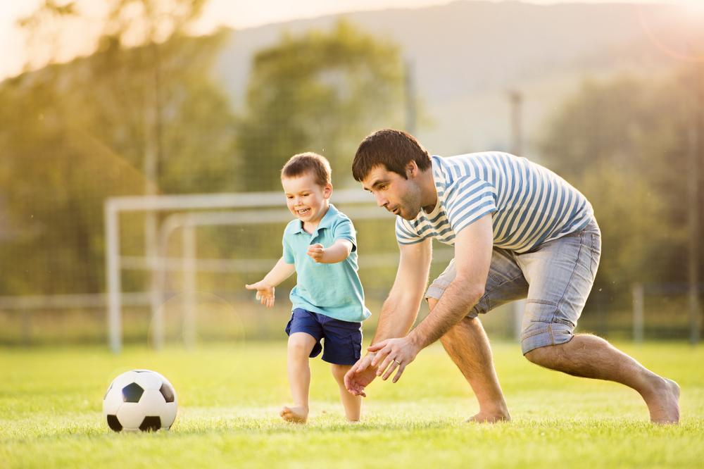 отец играет с сыном в футбол