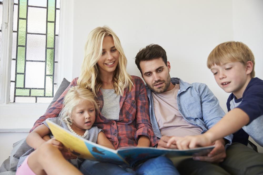 семья с детьми читает книгу