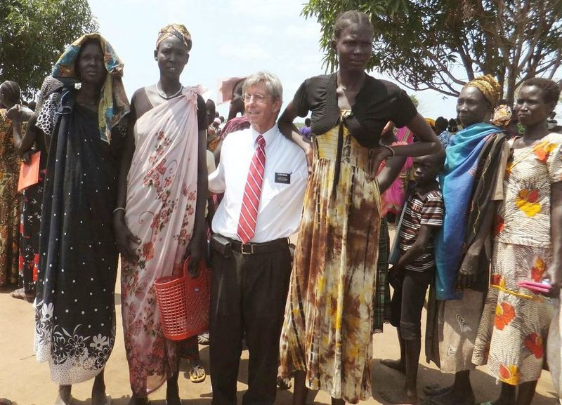 Representatives of the Dinka tribe next to a European