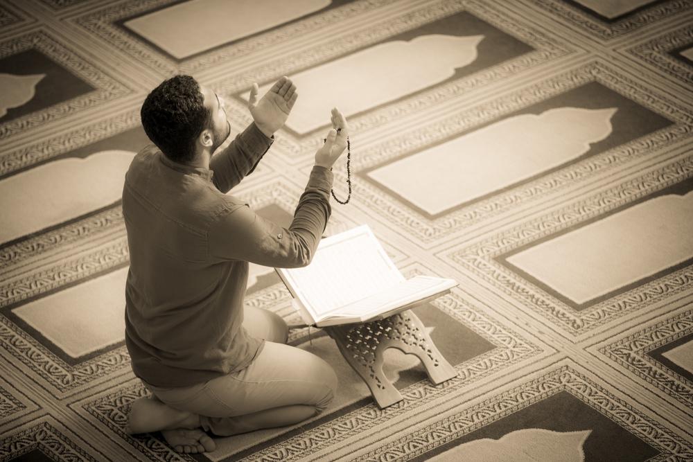 человек молится в мечети