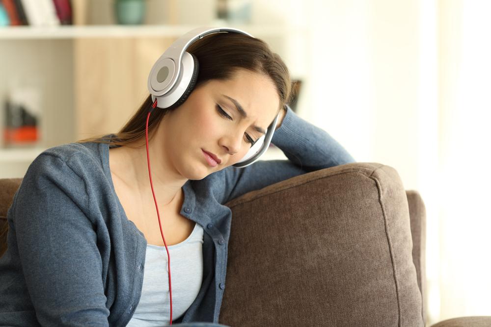 грустная девушка слушает музыку