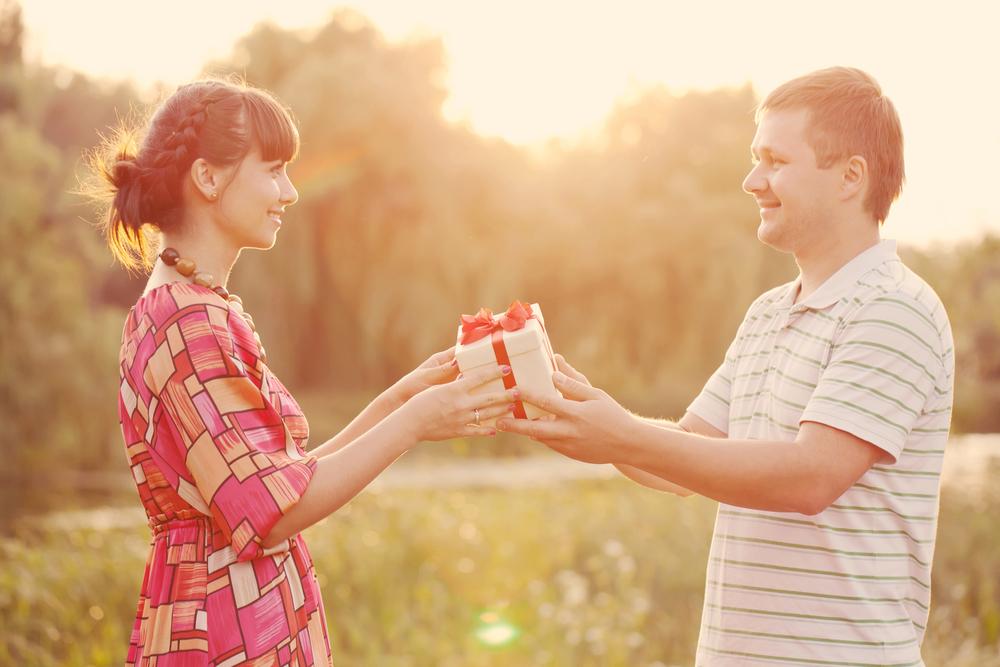 мужчина дарит подарок женщине