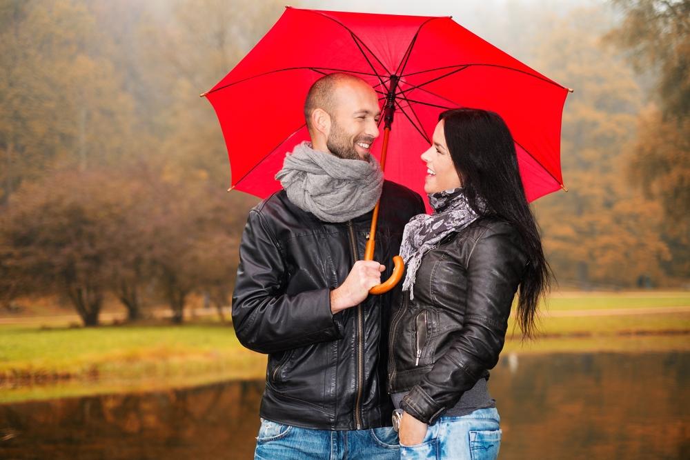 счастливая пара средних лет с зонтиком