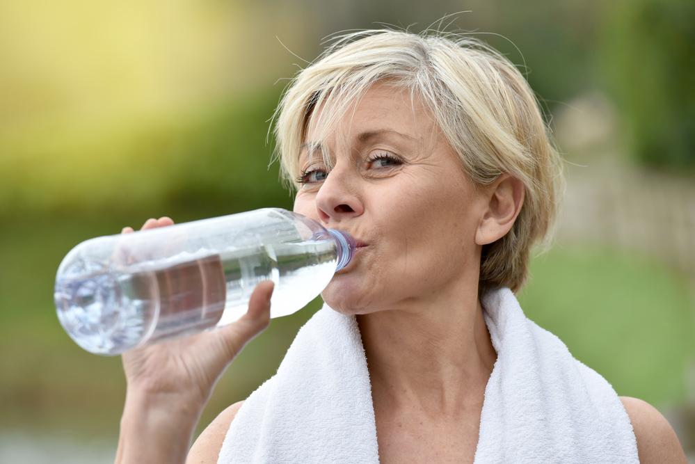женщина пьет воду после тренировки