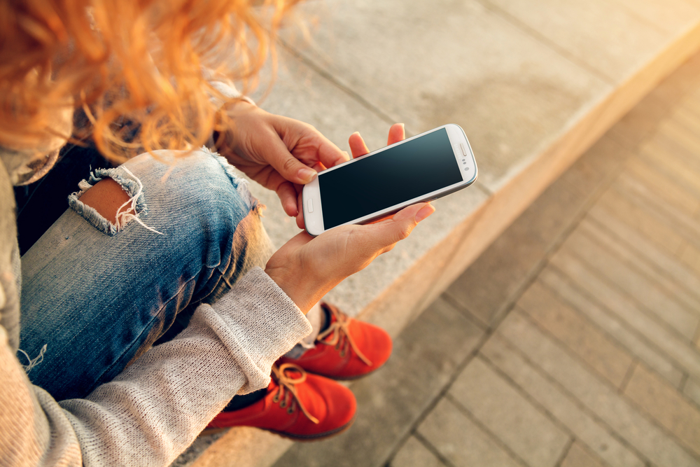 девушка держит в руке телефон