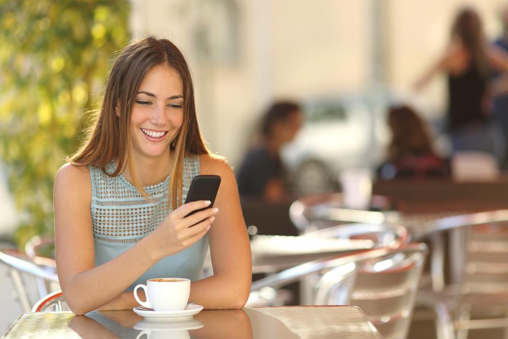 девушка улыбается глядя на телефон