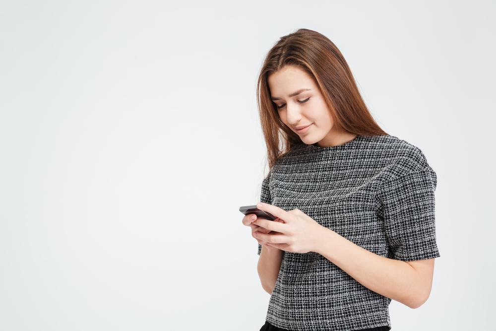 довольная девушка смотрит на телефон
