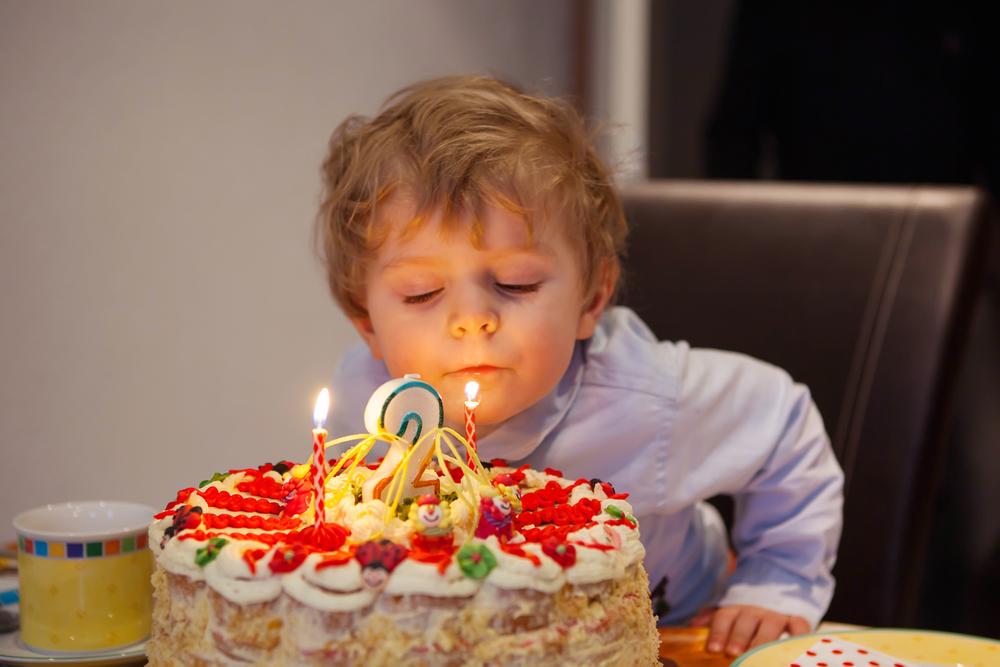 двухлетний мальчик задувает свечу на торте