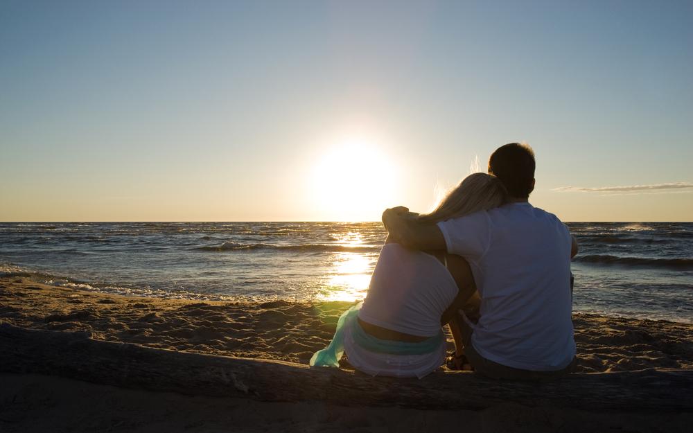 пара сидит на берегу моря
